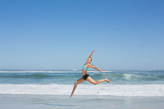 Fit woman jumping gracefully on the beach Royalty Free Stock Photos