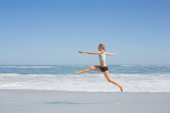 Fit woman jumping gracefully on the beach Stock Image