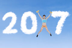 Fit woman jumping with 2017 Stock Photography