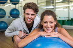 Fit woman leaning on exercise ball with trainer smiling at camera Stock Images