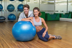 Fit woman leaning on exercise ball with trainer smiling at camera Royalty Free Stock Images