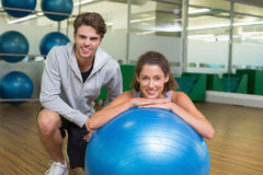 Fit woman leaning on exercise ball with trainer smiling at camera Stock Photo