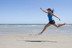Fit woman leaping mid air on a beach. Fit woman leaping mid air on the beach with ocean behind Stock Photo