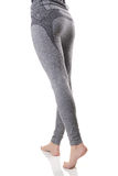 Fit woman legs with barefeet and buttocks from back side in gray sports thermal underwear with pattern. Sexy view of fit woman legs with barefeet and buttocks Stock Photography