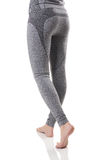 Fit woman legs with barefeet and buttocks doing step forward from back side in gray sports thermal underwear with pattern. Sexy view of fit woman legs with Royalty Free Stock Images