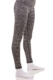 Fit woman legs wearing in grey sports thermal patterned pants in white socks Royalty Free Stock Photos