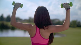 Fit woman lift weights outdoors. Back of woman exercising with dumbbells in park stock video footage