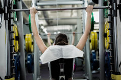 Fit woman lifting the barbell bench press royalty free stock image