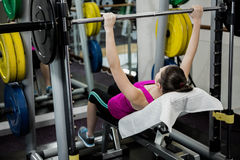 Fit woman lifting the barbell bench press royalty free stock photography