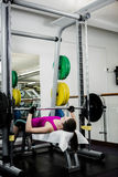 Fit woman lifting the barbell bench press stock photo