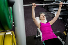 Fit woman lifting the barbell bench press royalty free stock photo