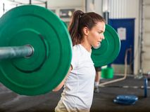 Fit Woman Lifting Barbell in Gym. Side view of fit young woman lifting barbell in cross training box Stock Image