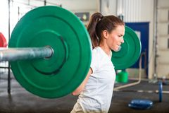 Fit Woman Lifting Barbell in Gym. Side view of fit young woman lifting barbell in fitness box Royalty Free Stock Photo