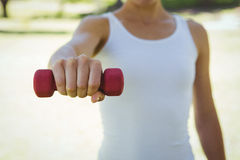 Fit woman lifting dumbbell in park Royalty Free Stock Images