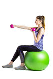 Fit woman lifting dumbbell sitting on ball Stock Photos