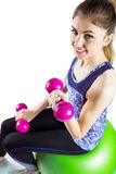 Fit woman lifting dumbbell sitting on ball Royalty Free Stock Photo