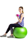 Fit woman lifting dumbbell sitting on ball Stock Image