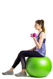 Fit woman lifting dumbbell sitting on ball Stock Photo