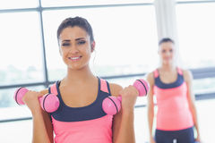 Fit woman lifting dumbbell weights with friend in background at gym Stock Photo