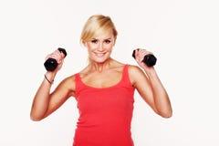 Fit woman lifting dumbbells stock photo