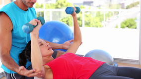 Fit woman lifting dumbbells on blue exercise ball with trainer. At the gym stock video