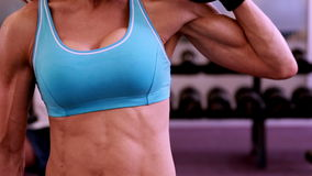 Fit woman lifting dumbbells at crossfit session. At the gym stock footage