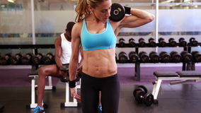 Fit woman lifting dumbbells at crossfit session stock video