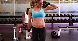 Fit woman lifting dumbbells at crossfit session stock video footage