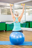 Fit woman lifting dumbbells and sitting on exercise ball Stock Images