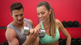 Fit woman lifting dumbbells with trainer stock video