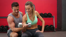 Fit woman lifting dumbbells with trainer. At a crossfit gym stock video