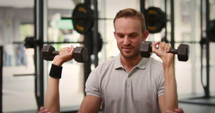 Fit woman lifting dumbbells with trainer. In high quality 4k format stock video footage