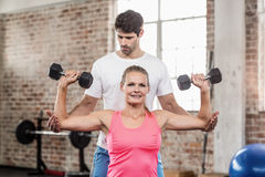 Fit woman lifting dumbbells with trainer. Fit women lifting dumbbells with trainer in crossfit gym Royalty Free Stock Image