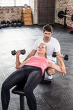 Fit woman lifting dumbbells with trainer. Fit women lifting dumbbells with trainer in crossfit gym Stock Images