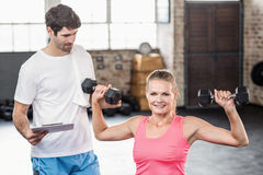 Fit woman lifting dumbbells with trainer. Fit women lifting dumbbells with trainer in crossfit gym Royalty Free Stock Photos