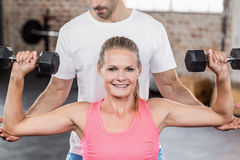 Fit woman lifting dumbbells with trainer. Fit women lifting dumbbells with trainer in crossfit gym Royalty Free Stock Photo