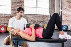 Fit woman lifting dumbbells with trainer. Fit women lifting dumbbells with trainer in crossfit gym Stock Photography