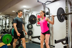 Fit woman lifting heavy barbell in weights room Royalty Free Stock Photo
