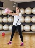 Fit Woman Lifting Kettlebell In Health Club Royalty Free Stock Photos
