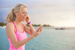 Fit woman listening to music while working out stock image