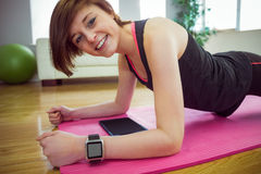 Fit woman looking at camera and doing plank on mat Royalty Free Stock Image