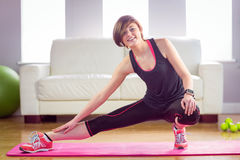 Fit woman looking at camera and stretching on exercise mat Stock Photography