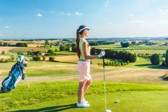 Fit woman looking at the horizon on the green grass of a golf course. Side view of a fit woman wearing modern golf outfits, while looking at the horizon on the Stock Image