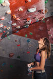Fit woman looking up at rock climbing wall Royalty Free Stock Images