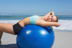 Fit woman lying on exercise ball at the beach stretching Stock Images