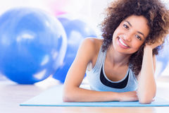 Fit woman lying on exercise mat in fitness studio Stock Photos