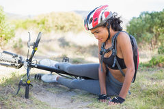 Fit woman lying on ground after bike crash Stock Images