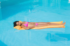 Fit woman lying on lilo in swimming pool Stock Photos