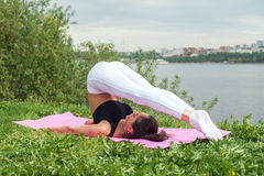 Fit woman making yoga in plow pose on mat in nature. Stock Images
