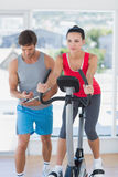 Fit woman with male instructor working out at spinning class Royalty Free Stock Photo